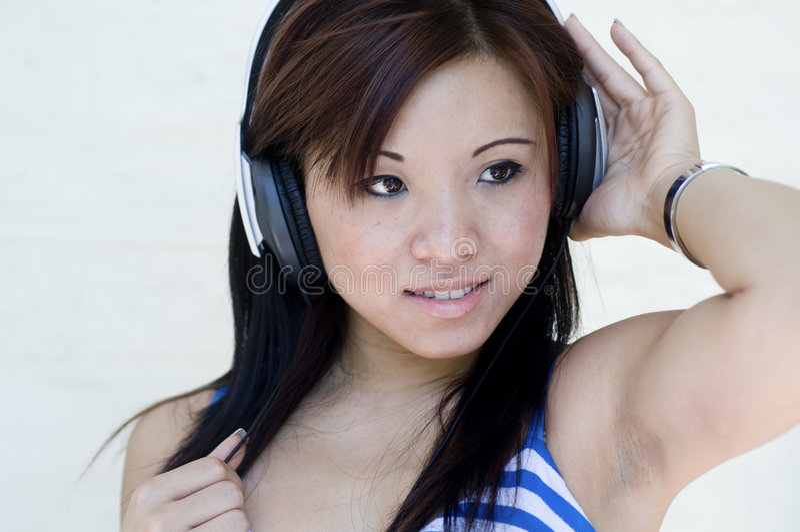 Mulher bonita que escuta a música com auscultadores imagem de stock