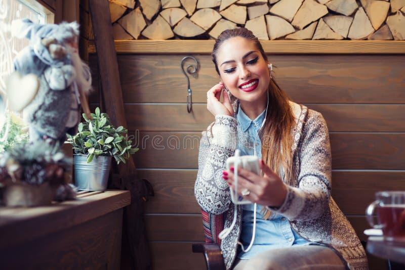 A mulher bonita que escuta a música com fones de ouvido ao beber o café com sentimento feliz e relaxa no café foto de stock royalty free