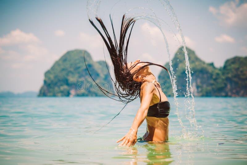 Mulher bonita que espirra a água do mar com seu cabelo imagens de stock royalty free