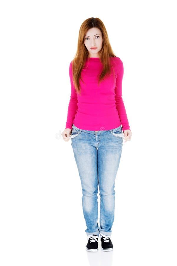 Mulher bonita que está e que mostra lhe bolsos vazios. fotografia de stock royalty free