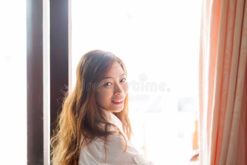 Mulher bonita que está a menina asiática nova da janela próxima imagem de stock