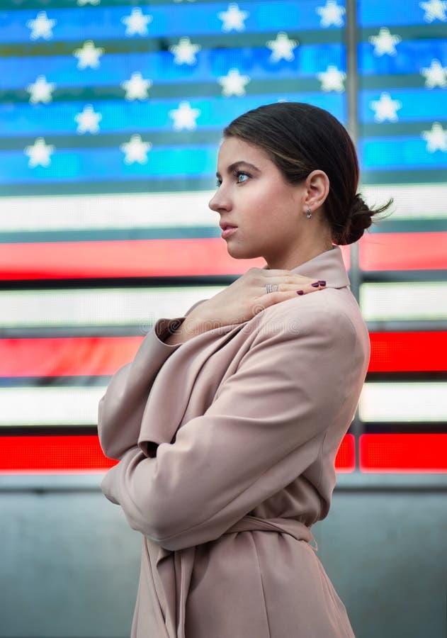 Mulher bonita que está na frente da bandeira americana e que olha ao lado Conceito do patriotismo da nação dos povos foto de stock royalty free