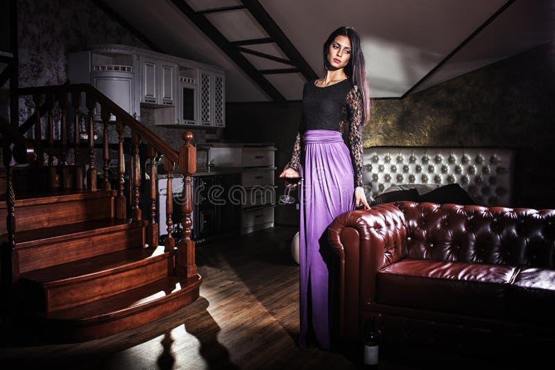 Mulher bonita que está o sofá de couro próximo do vintage imagens de stock