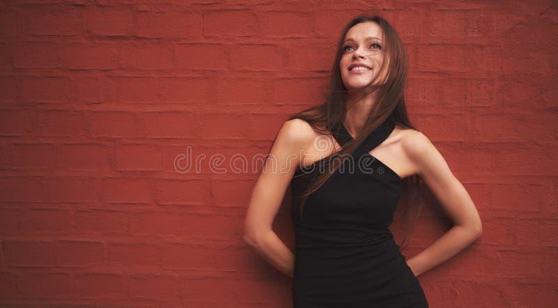 Mulher bonita que está perto da parede de tijolo vermelho foto de stock royalty free