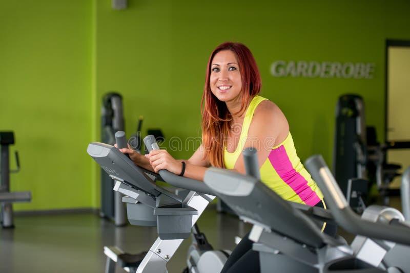 Mulher bonita que exercita em uma bicicleta de exercício fotos de stock