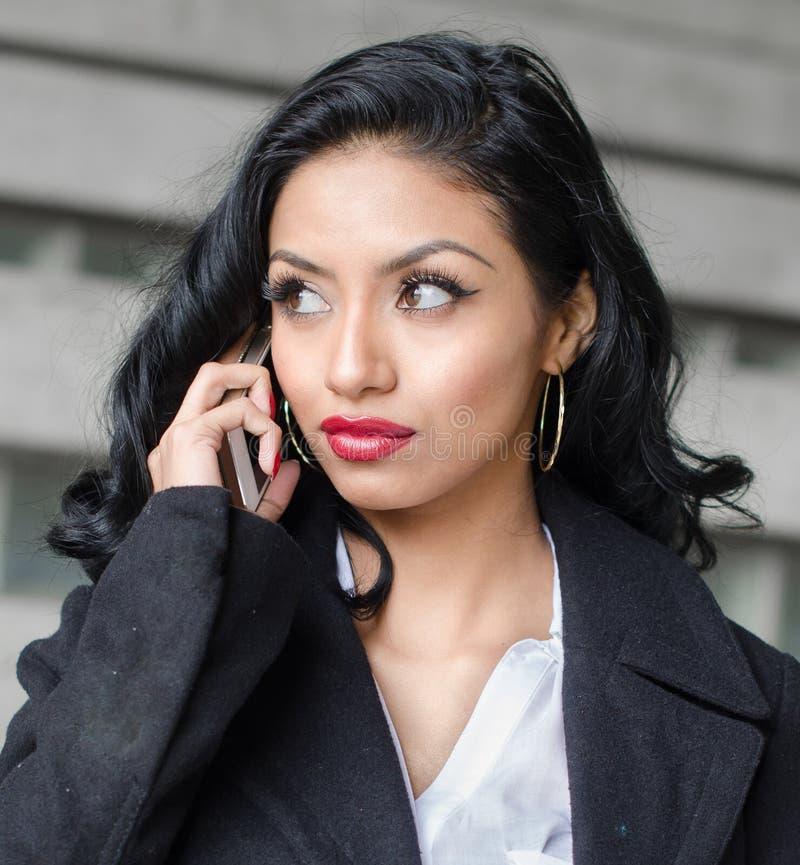 Mulher bonita que fala no telefone foto de stock royalty free