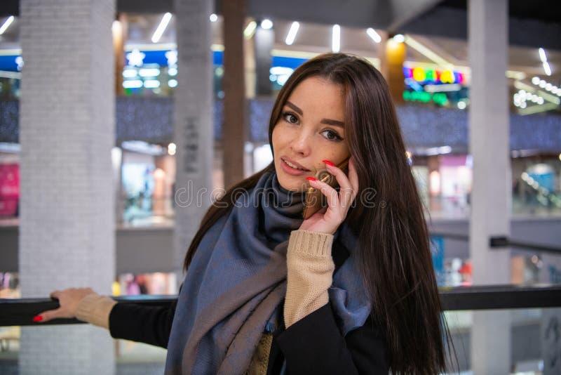 Mulher bonita que fala no telefone ao sair em shopping spree imagem de stock royalty free