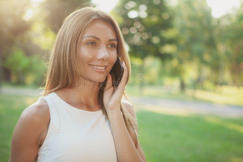 Mulher bonita que fala no telefone fora imagem de stock