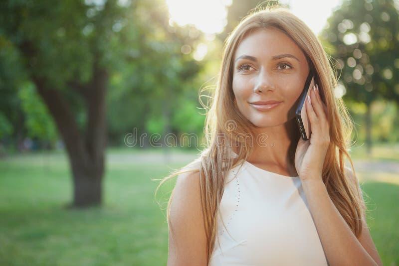 Mulher bonita que fala no telefone fora imagem de stock royalty free