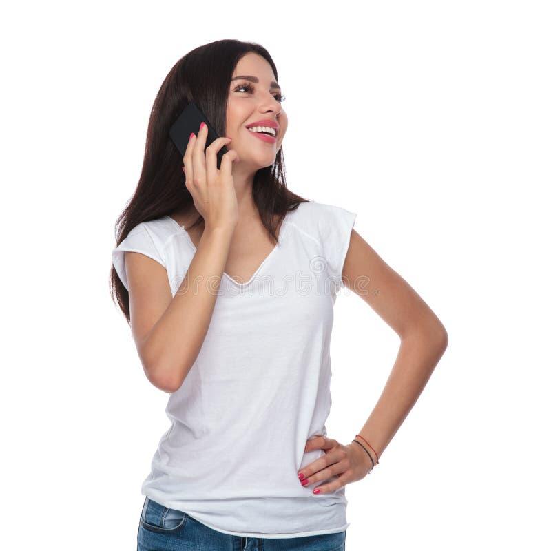 A mulher bonita que fala no telefone olha acima para tomar partido imagens de stock