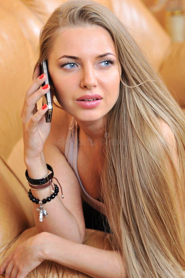 Mulher bonita que fala pelo telefone celular dentro fotografia de stock