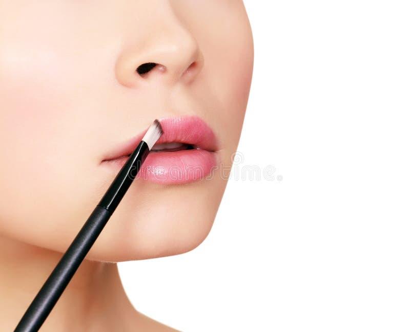 Mulher bonita que faz a composição na cara com escova cosmética fotos de stock