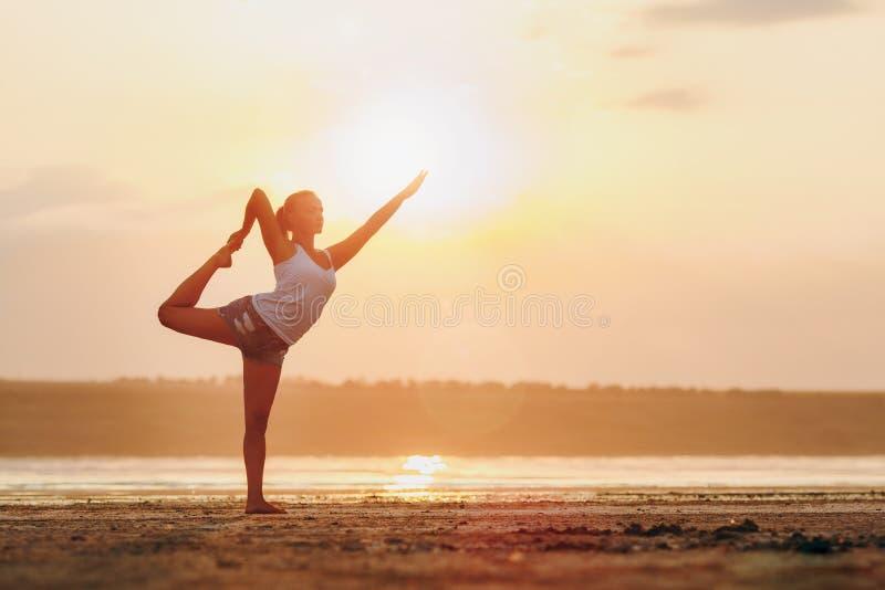 Mulher bonita que faz a ioga no por do sol fora imagens de stock