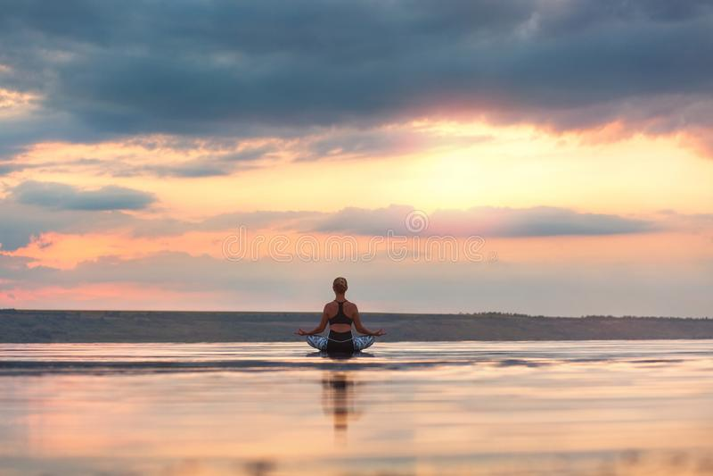 Mulher bonita que faz a ioga no por do sol fora foto de stock