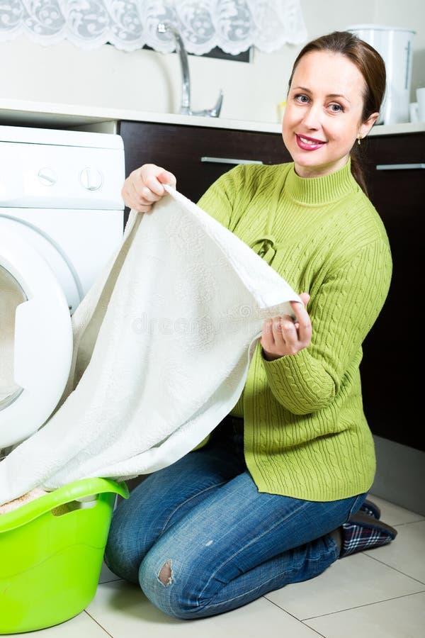 Mulher bonita que faz a lavanderia imagem de stock