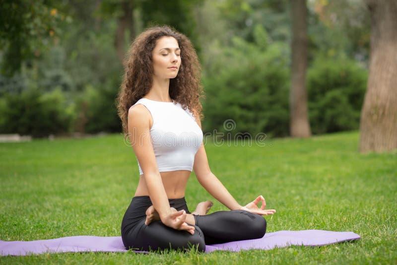 Mulher bonita que faz a meditação da ioga nos lótus foto de stock