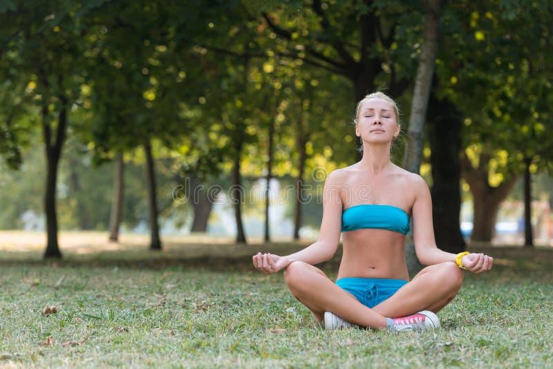 Mulher bonita que faz o asana da pose da ioga imagem de stock royalty free