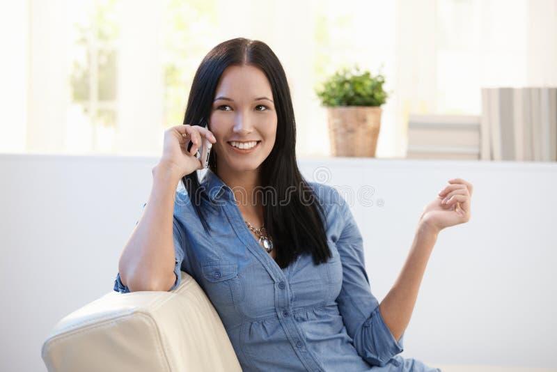 Mulher bonita que faz o atendimento de telefone imagem de stock