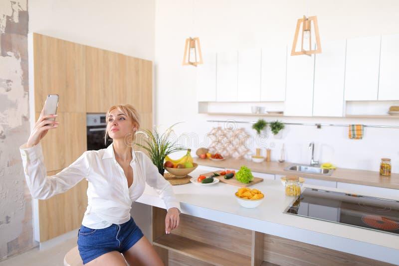 Mulher bonita que faz o selfie no telefone no fundo da cozinha t foto de stock royalty free