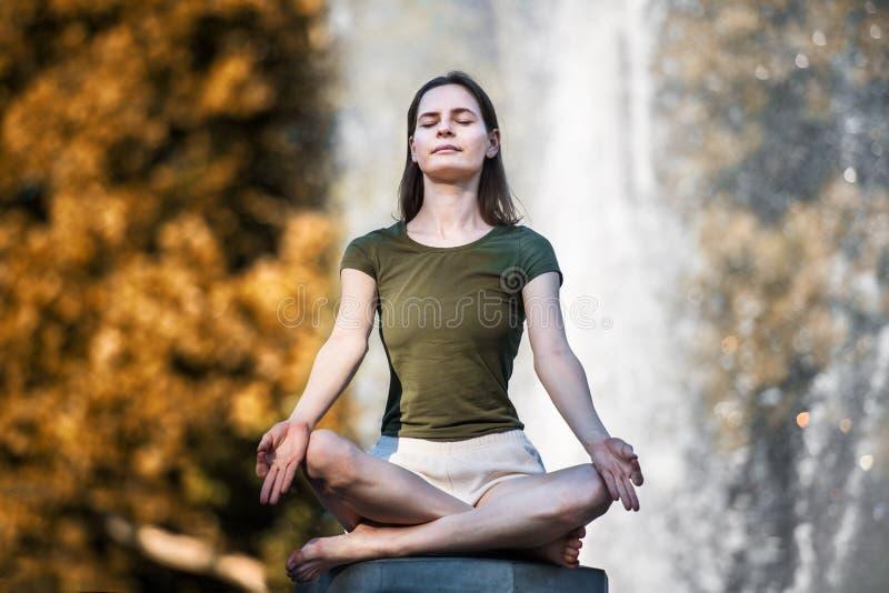 A mulher bonita que faz a pose da ioga no parque da cidade e aprecia o estilo de vida saudável fotografia de stock