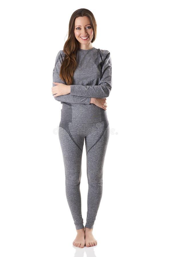 A mulher bonita que fica de aperto com seus braços no cinza ostenta o roupa interior térmico imagem de stock