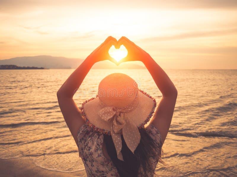 Mulher bonita que guarda as mãos no ajuste de quadro da forma do coração durante o por do sol na praia do oceano fotos de stock royalty free
