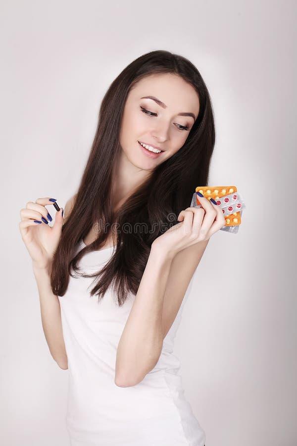 Mulher bonita que guarda comprimidos de controlo da natalidade, contraceptivo oral imagem de stock