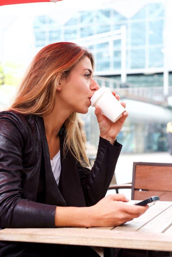 Mulher bonita que guarda o café bebendo do telefone esperto fotos de stock