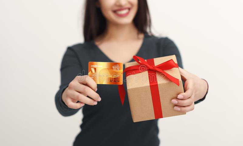Mulher bonita que guarda o cartão e a caixa de presente de crédito fotos de stock royalty free