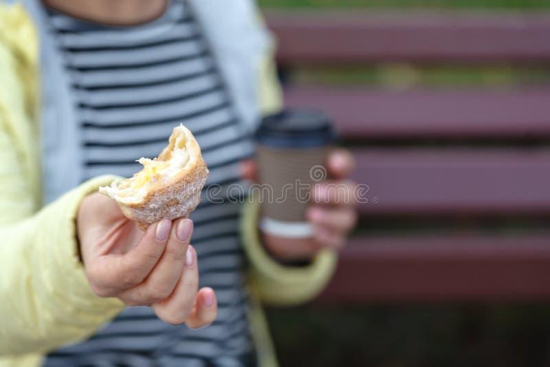 Mulher bonita que guarda o copo e o croissant de café fotografia de stock royalty free