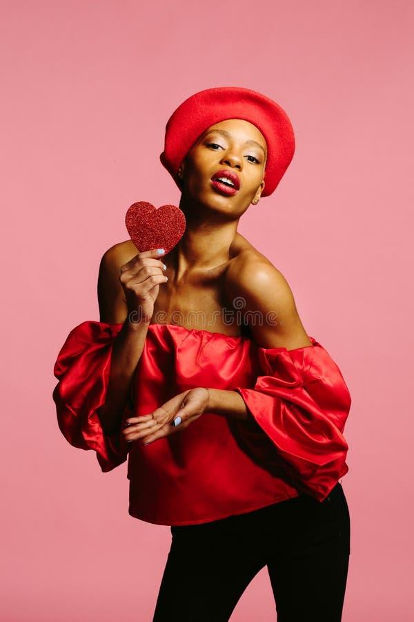 Mulher bonita que guarda o coração vermelho que envia o beijo imagens de stock
