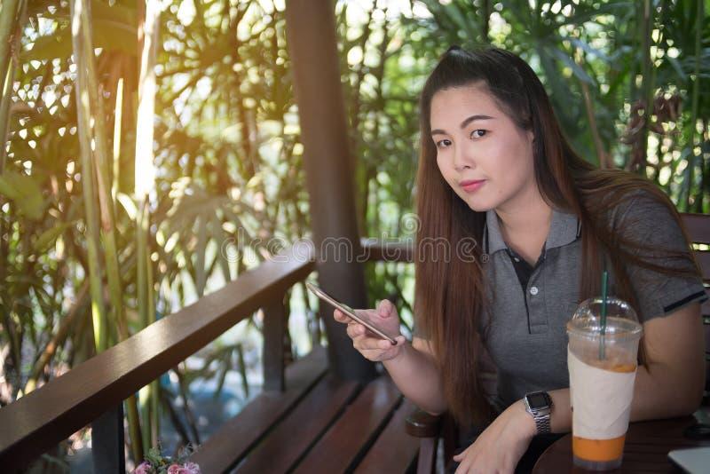 Mulher bonita que guarda o telefone celular e que olha a câmera no co fotografia de stock