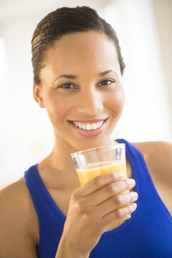 Mulher bonita que guarda o vidro de Juice At Gym alaranjado foto de stock