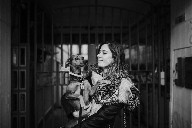 Mulher bonita que guarda seu cão com um sorriso fotos de stock royalty free