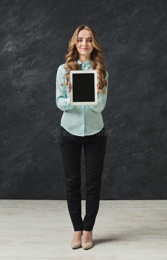 Mulher bonita que guarda a tabuleta digital no estúdio fotos de stock royalty free