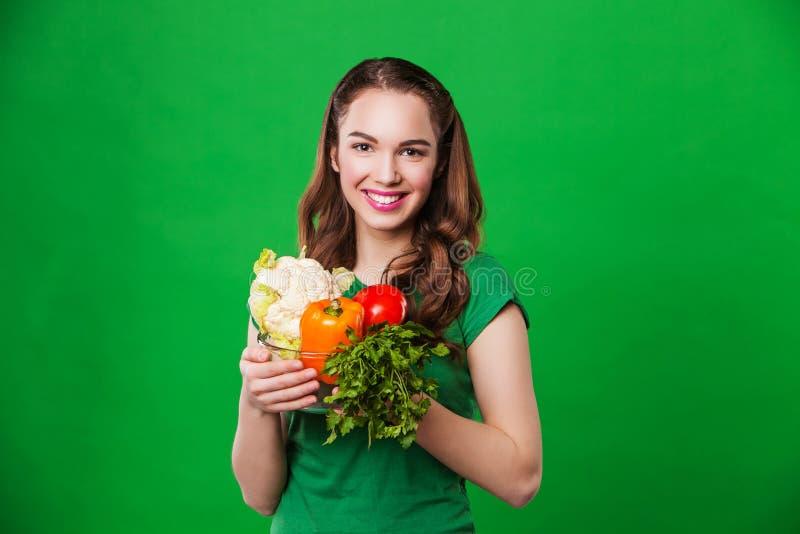 Mulher bonita que guarda um alimento fresco e saudável No fundo verde imagens de stock royalty free