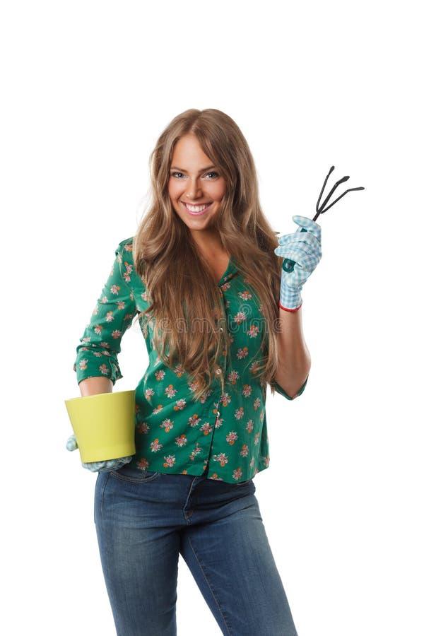 Mulher bonita que guarda um ancinho de jardinagem imagens de stock