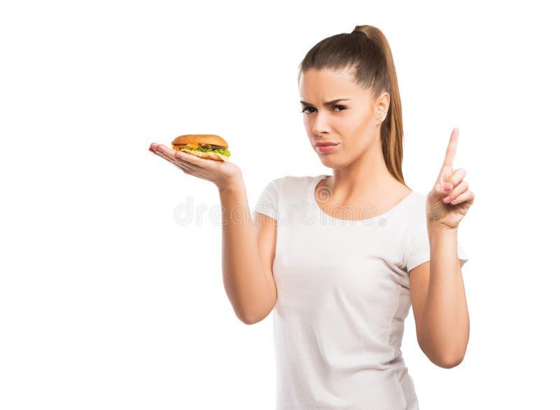 Mulher bonita que guarda um cheeseburger, dizer NÃO ao alimento insalubre foto de stock royalty free