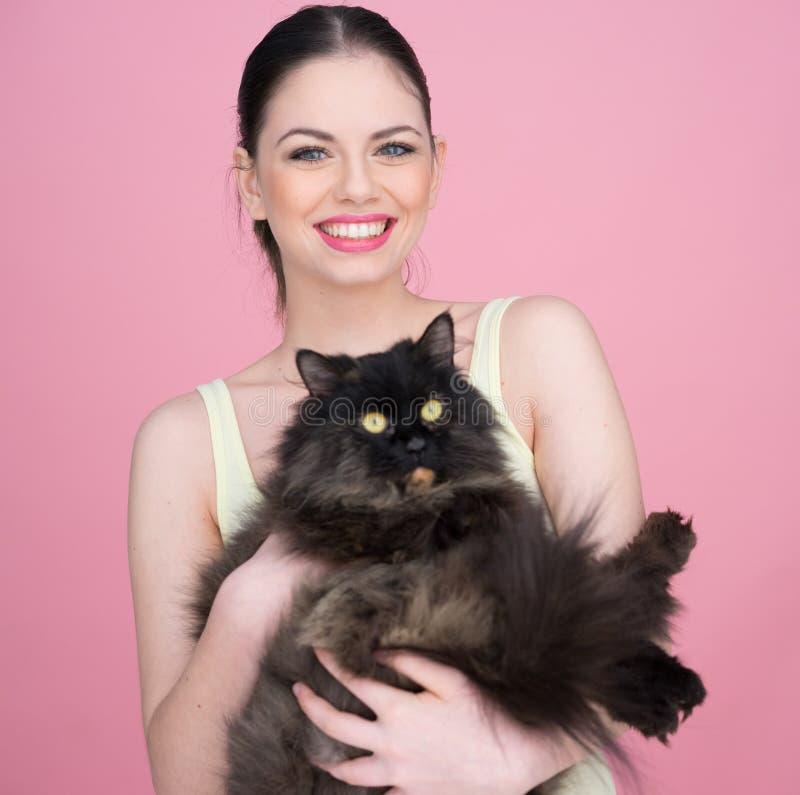 Mulher bonita que guarda um gato preto grande fotografia de stock royalty free