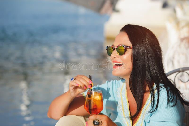 Mulher bonita que guarda um vidro do cocktail no café do beira-mar imagem de stock royalty free