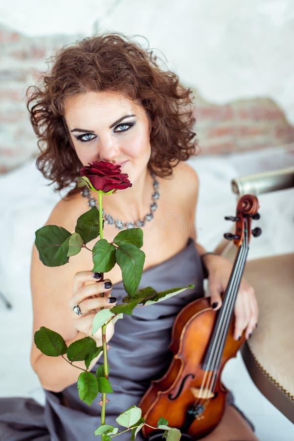Mulher bonita que guarda um violino e que cheira a rosa do vermelho fotos de stock royalty free