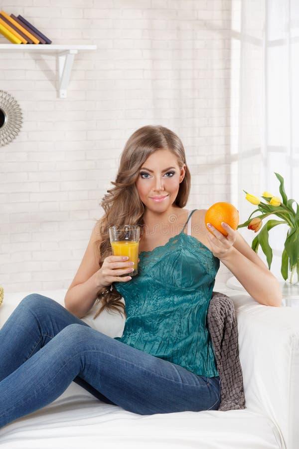 Mulher bonita que guarda uma laranja e um vidro do suco fotos de stock