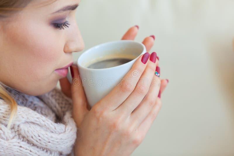 Mulher bonita que guarda uma xícara de café em suas mãos em uma camiseta bege feita malha imagem de stock royalty free