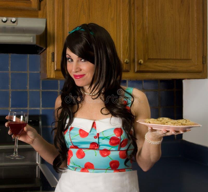 Mulher bonita que guardara o vinho e os biscoitos fotografia de stock royalty free