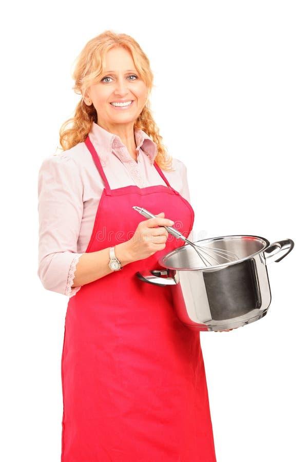 Mulher bonita que guardara um potenciômetro e um utensílio da cozinha fotos de stock