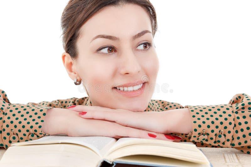 Mulher bonita que inclina-se no livro que olha de lado imagem de stock