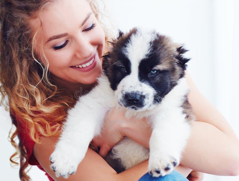 Mulher bonita que joga com o cachorrinho caucasiano bonito do pastor, cão foto de stock royalty free