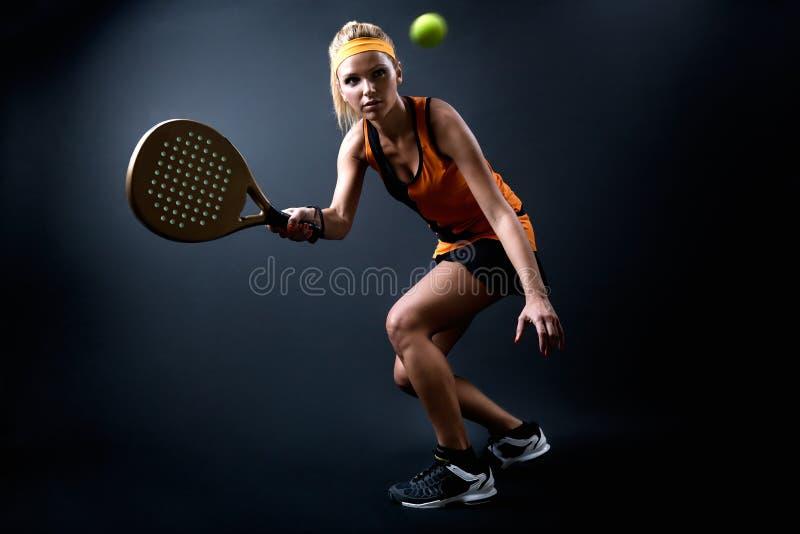 Mulher bonita que joga o padel interno Isolado no preto fotos de stock royalty free