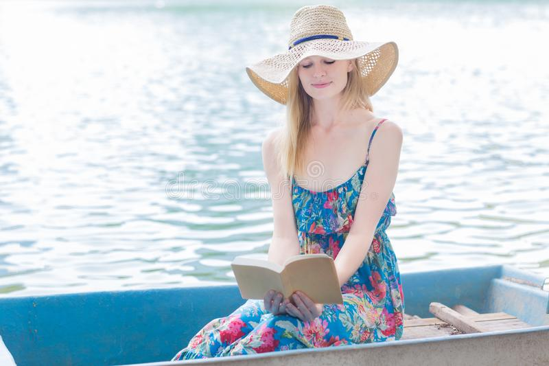 Mulher bonita que lê em seguido o barco em um lago foto de stock royalty free