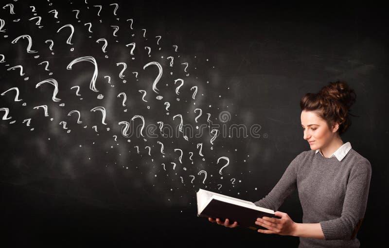 Mulher bonita que lê um livro com os pontos de interrogação que saem de imagem de stock